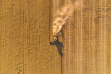 Bird's Eye View Of A Header Harvesting A Barley Crop In The Late Afternoon.