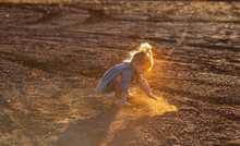 Little Kid Playing In The Dirt With Backlight Highlighting Dust
