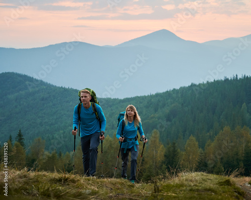 Two persistent professional hikers with trekking poles and backpacks moving on mountain hills against a background of green forest, mountain beskids and purple sky looking ahead Fototapet