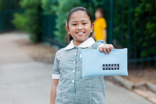 Aussie Kid Of Filipino Ethnicity Holding Out A Pencil Case Ready For Going Back To School
