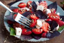 Salad With Strawberries, Cherry Tomatoes, Sunflower Seeds, Basil And Feta Cheese On Dark Brown Background.  Strawberry And Feta Cheese On Fork