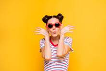 Photo Of Pretty Childish Young Woman Wear Striped T-shirt Dark Glasses Dancing Arms Ears Lips Pouted Isolated Yellow Color Background