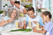 Happy Grandmother And Grandchildren Having Breakfast Together In Kitchen