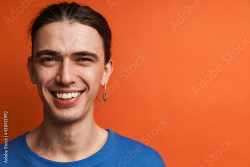 Billede på lærred Young white man with earring looking and laughing at camera