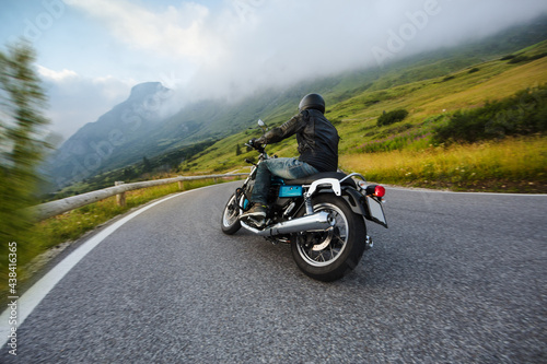 Motorcycle driver riding in Alpine landscape. Lifestyle photo with motion blur effect and copyspace. #438416365