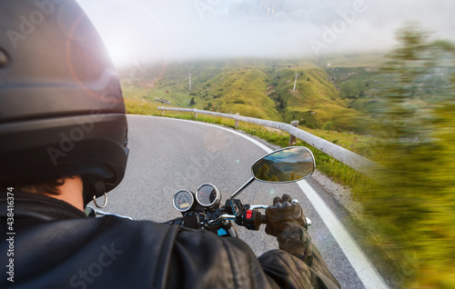 Motorcycle driver riding on mountains highway, handlebars view, Dolomites, central Europe. #438416374