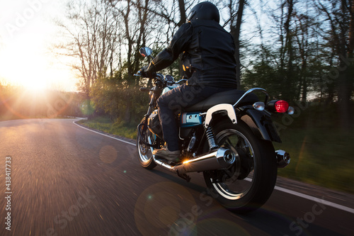 Motorcycle driver riding in Alpine landscape. Lifestyle photo with motion blur effect and copyspace. #438417733