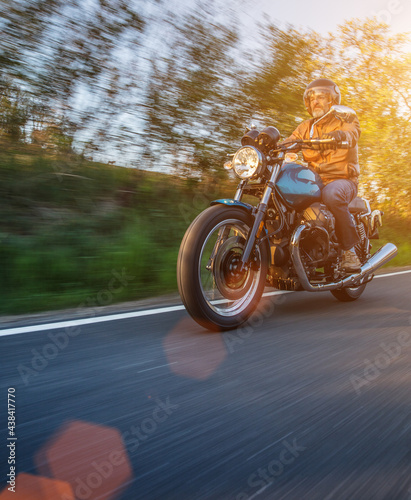 Motorcycle driver riding in Alpine landscape. Lifestyle photo with motion blur effect and copyspace. #438417770
