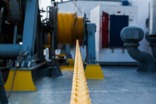 Marine Hydraulic Winch For Mooring Operations With Yellow Ropes Wound Around It.