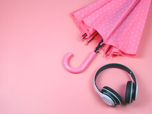 Flat Lay  Of Headphones And Pink Polka Dot Umbrella On Pink Background With Copy Space. Music And Rainy Season Concept.
