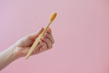 Daily Human Hygiene, Cotton Swabs And Cotton Pads, A Woman's Hand Holding Bamboo Toothbrushes On A Pink Background In A Glass Or Against A Background Of Plants, Eco-friendly Personal Hygiene Products