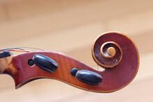 Vintage Brown Violin Head Music Instrument Close Up On Light Brown Background