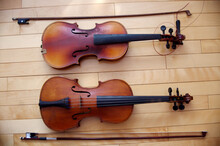 Two Vintage Brown Violins Music Instruments On Wood Floor Background