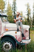 Man Sitting On Rusty Car In Countryside