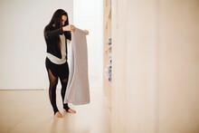 Woman Folding Blanket In Closet