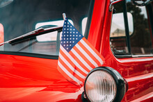 Red Pickup Truck With Small American Flag Waving. Close Side View Of Red Pickup Truck American Flag Waving. 4th Of July Holiday. American Flag Blowing In The Wind. Independence Day
