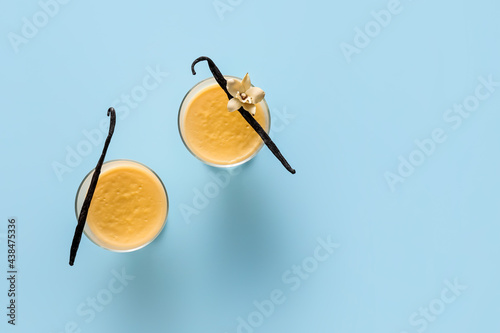 Obraz na plátně Glass bowls with tasty vanilla pudding on color background