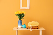 Vase With Yellow Roses And Clothes On Table Near Color Wall