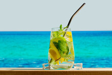 Glass Of Mojito Cocktail On Tropical Beach. Refreshing Summer Drink With Lemon, Lime And Mint, Blue Sea On Background. Summer Resort, Beach Bar Concept.