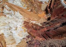 Aerial View Of The Inside Of A Mine In Arizona. Textured Dirt In Red, Orange, White, And Pink Hues.