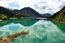 Green Water Lake With Reflections Of Blue Sky And White Clouds And View To Wooded Mountains In The Back