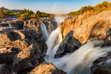 A Rainbow Glistens In The Spray From Epupa Falls, The Multiple Rivulets Blurred With A Slow Shutter Speed, Capture In Soft And Warm Evening Light, Namibia Angola Border, Kunene River.