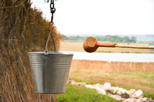 A Water Fountain With An Old Bucket And A Makeshift Mug Made Of Pumpkin. Reed Fence In Background. Traditions And Lifestyle.