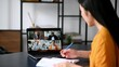 Video conference, distant learning, online working. Successful asian female student or freelancer, studies or works remotely, watches an online lecture, takes notes,multiracial people on laptop screen