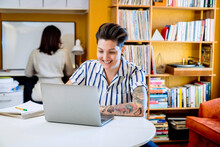 Smiling Woman Working On Laptop While Wife Works Behind Her