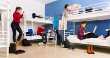 Cheerful Positive Men And Women Friendly Interacting While Staying In Modern Comfy Hostel