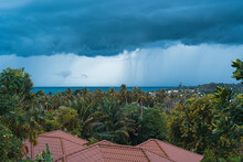 Rain And Storm Comes Over A Forest Valley, Sea And Rooftops On A Summer Day On A Tropical Island. View From The Balcony
