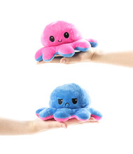 The Hand Holds A Cheerful And Sad Soft Toy. Happy And Sad Octopus. Close Up. Isolated On A White Background