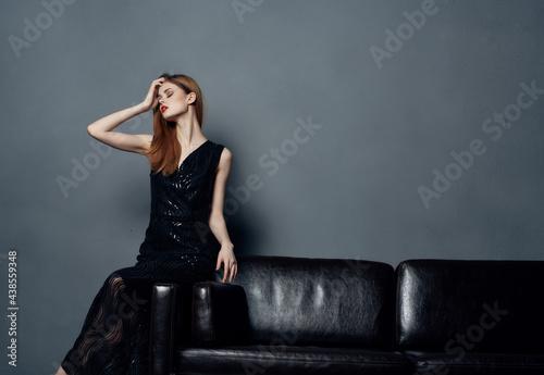 Fototapeta woman on evening black dress sitting on sofa posing luxury interior