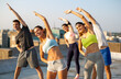 Leinwandbild Motiv Group of happy friends working out together outdoors. Fitness, training, sport and people concept