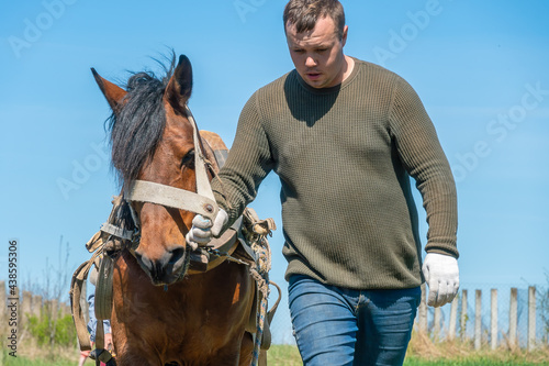 Photo Man holds a horse by the bridle and leads it through a field on a sunny day