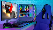 Colorful Bright Illuminated Rgb Gaming Pc With Keyboard Mouse Monitor And Chair With Racing  Screen In Front Of LED Light Brick Stone Wall. Computer Playing Hardware Games Background