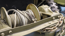 A Detailed Photo Of An Automotive Mechanical Winch With A Cable. A Rusty Old Tow Rope Attached To A Heavy Duty Military Vehicle.