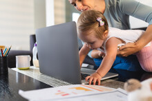 Caucasian Mother Holding Her Baby While She Tries To Touch The Laptop At Home