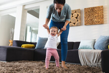 Caucasian Mother Teacher Her Baby To Walk At Home