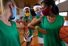 Diverse Female Basketball Team Wearing Face Masks And Greeting With Elbows