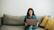 Leinwandbild Motiv Happy businesswoman with laptop sitting in lobby