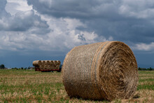 A Hay Bale In The Foreground With A Trailer Full Of Other Bales In The Background Under A Dramatic Sky, Bientina, Pisa, Italy