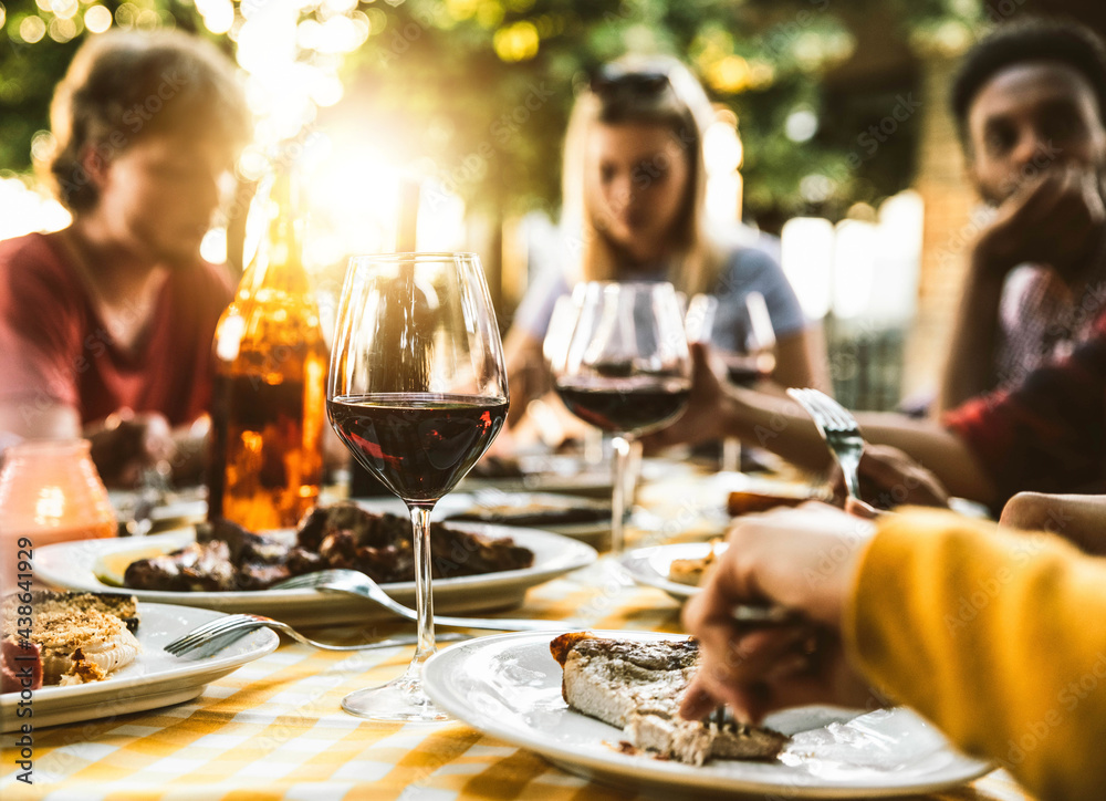 Leinwandbild Motiv - Davide Angelini : Group of friends having bbq dinner outdoor in garden restaurant - Multiracial family eating food at barbecue backyard home party - Focus on wine glass