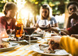 Leinwandbild Motiv Group of friends having bbq dinner outdoor in garden restaurant - Multiracial family eating food at barbecue backyard home party - Focus on wine glass