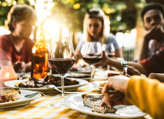 Group of friends having bbq dinner outdoor in garden restaurant - Multiracial family eating food at barbecue backyard home party - Focus on wine glass