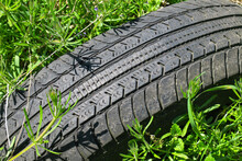 Old Black Car Tire In The Grass