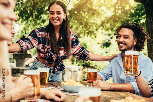 Fototapeta Happy friends celebrating drinking beer pint outdoor - Young people talking and