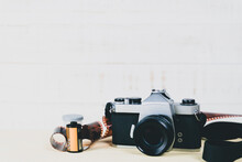 Old 35mm SLR Film Camera And A Roll Of Film On Wooden Background. Flim Photography Concept.