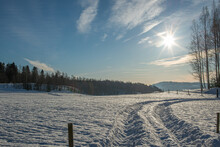 A Large Deep Snow Covered Field With Deep And Wide Tractor Trails Leading Away From Camera, Blue Sky And Sun High In The Sky, Forest Hill In The Distance