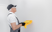 Concept Building, Painter In Gloves And Uniform Holding Painting Roller Repair Apartment Home